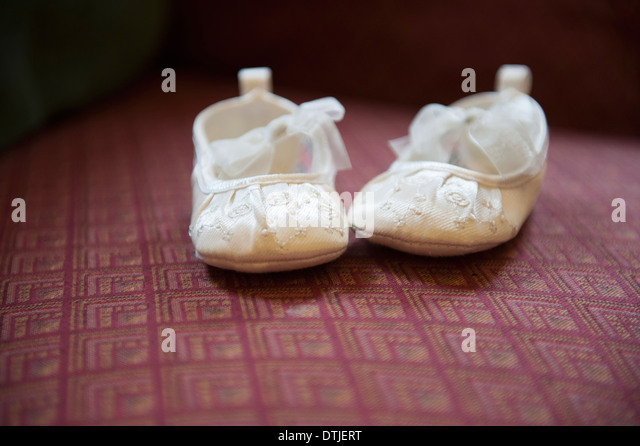 A pair of cream-coloured embroidered satin Christening boots with lace ribbon bows England - Stock Image