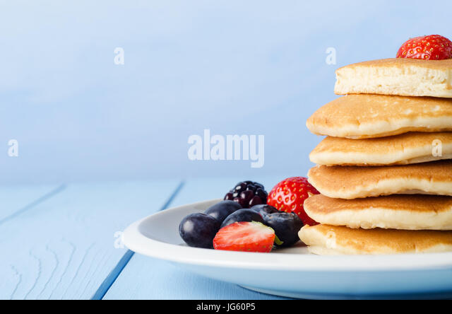 A stack of breakfast pancakes topped with a strawberry, standing on a white china plate, surrounded by Summer fruits. - Stock Image