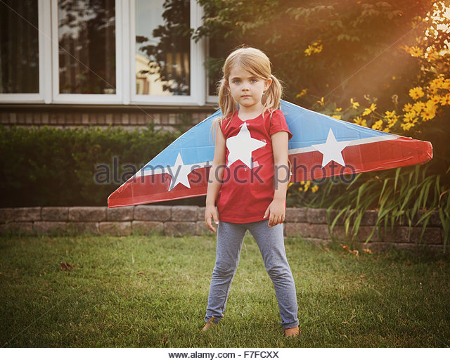 A little child is wearing homemade cardboard flying wings with stars on them pretending to be a pilot for a craft, - Stock Image