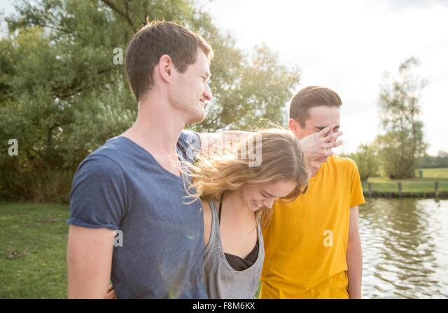 Group of young adults, standing by lake, fooling around, laughing - Stock Image