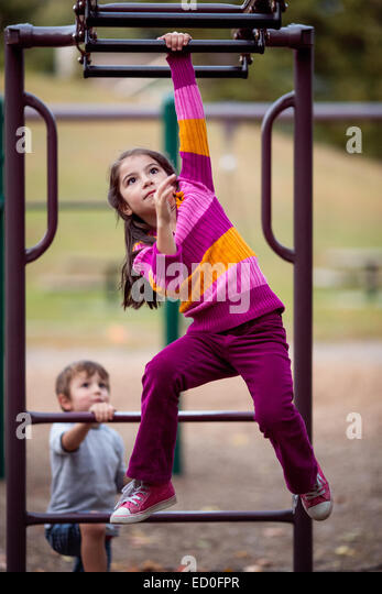 Girl and boy playing on climbing frame - Stock Image