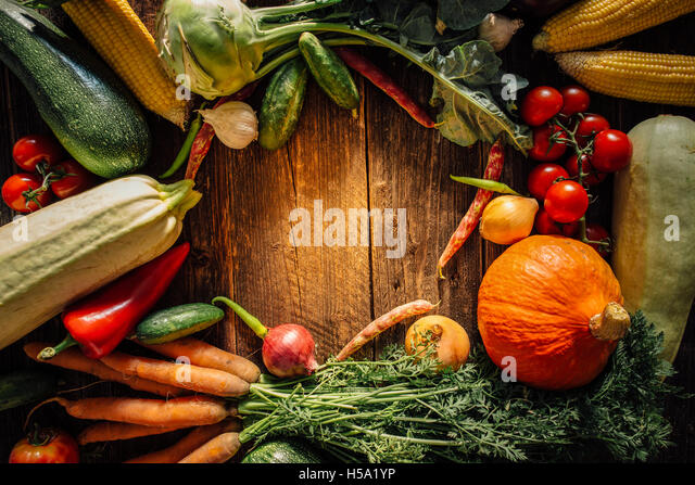 Frame of various vegetables over wooden table with copy space - Stock Image
