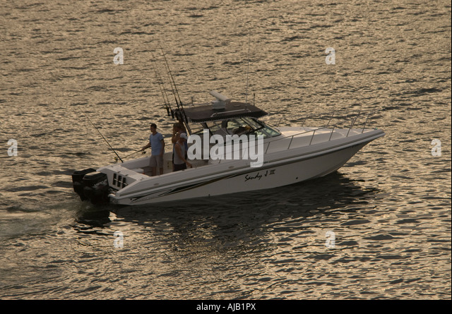 fishing and boating near twilight with outboard motor trolling slowly - Stock Image