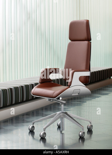 Brushed steel and brown leather luxury office chair on dark steel parquet floor design furniture - Stock Image