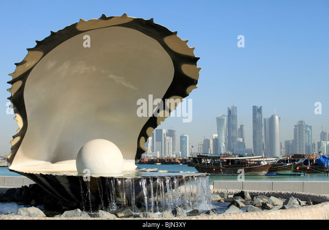 The oyster and pearl fountain on the Corniche in central Doha, Qatar, with the Dhow harbour and the new skyline - Stock Image