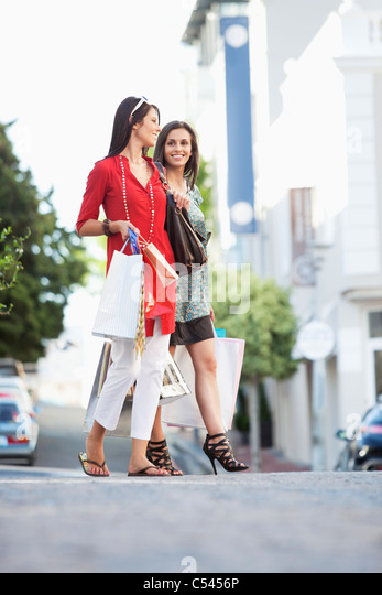 Two young women walking with shopping bags - Stock Image