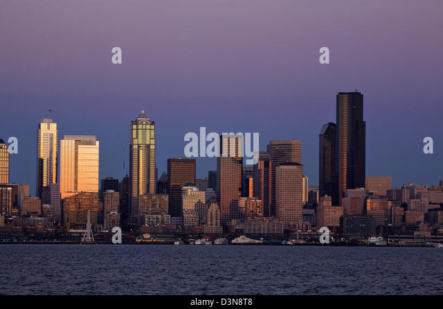 The highrises of downtown Seattle and the waterfront, including the Great Wheel, on Elliot Bay at dusk from West - Stock Image