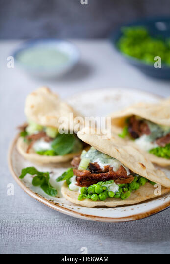 Mini flat breads with crispy lamb, mashed peas, cucumber, mint and yogurt sauce - Stock Image