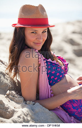 Smiling woman wearing sun hat on beach - Stock Image