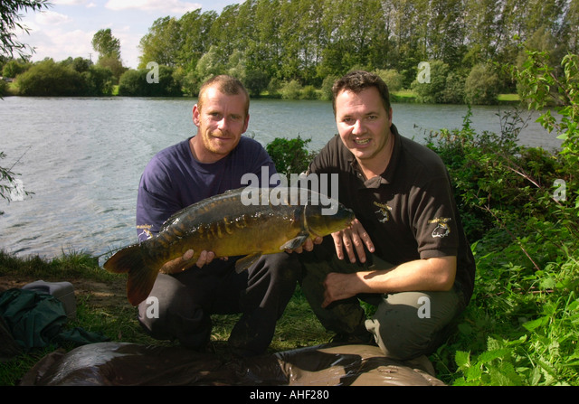 British Carp Angling Championship final Tim Fromant right Mike Winstone with a large mirror carp weighing 13lbs - Stock Image