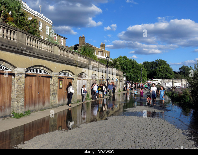 People walking around Thames River high tide overflow on a summer evening in Richmond, London. - Stock Image