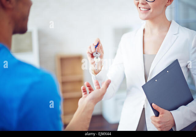Smiling woman giving buyer key from new residence - Stock Image