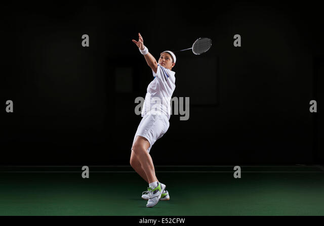 Side view of young woman in sportswear playing badminton isolated over black background - Stock Image