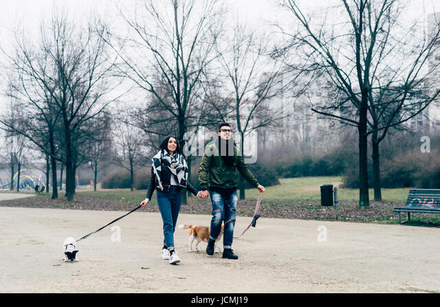 Young couple walking outdoor with dogs on a leash smiling - friendship, everyday life, happiness concept - Stock-Bilder