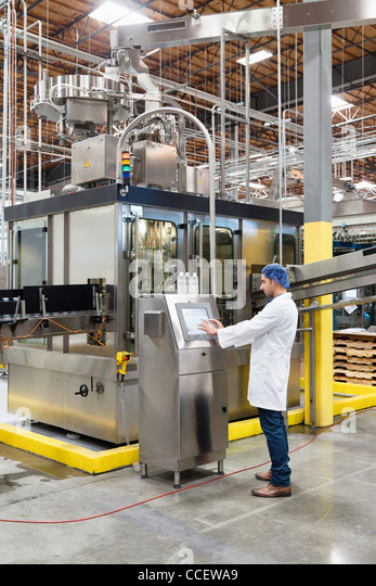 Man working on machinery in bottling industry - Stock Image