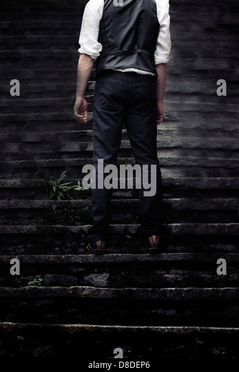 a man standing on old stone steps - Stock Image