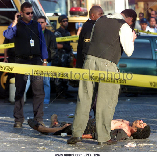 Venezuelan authorities examine the body of a man hit by a suspected  bomb in Caracas January 23, 2003. One person - Stock Image