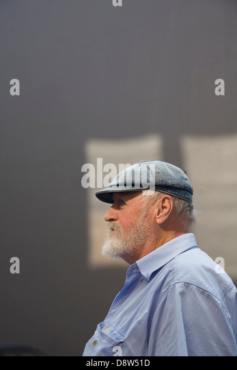 Man 50s, with grey beard, wearing cloth cap and blue shirt, against grey wall with patches of sunlight, in profile - Stock Image