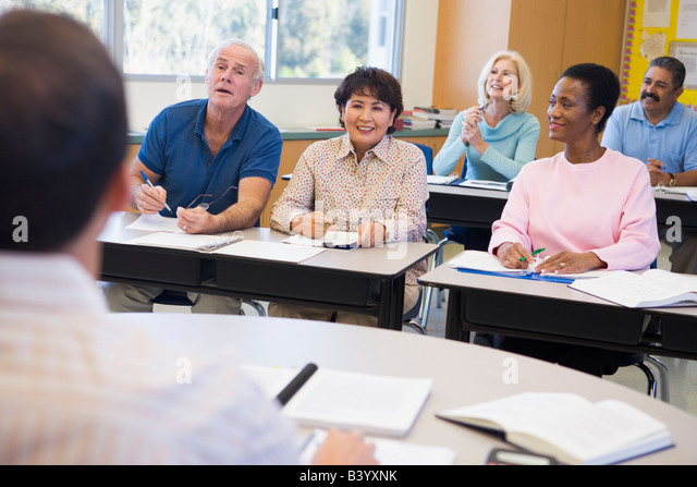 Adult students in class with teacher (selective focus) - Stock Image
