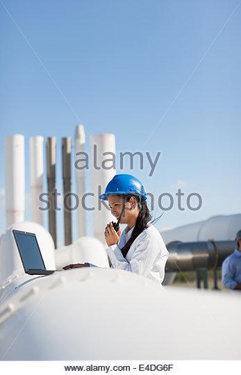 Businesswoman in hard-hat talking walkie-talkie &  using laptop - Stock Image
