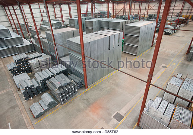 Steel tubing and finished safety barriers in warehouse - Stock Image