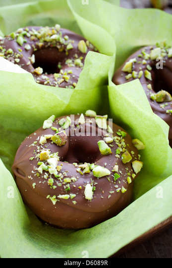 Chocolate donuts with crushed pistachios on top - Stock Image