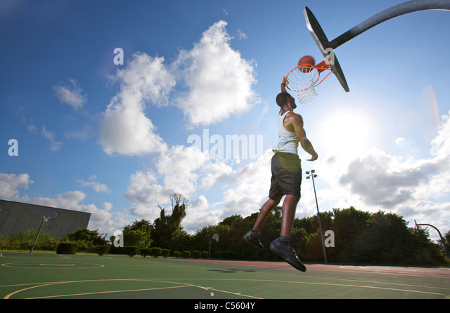 male making slam dunk during outdoor basketball game, upward view - Stock Image