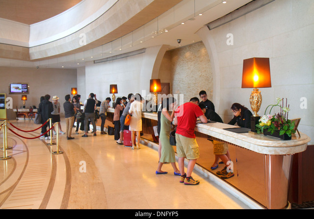 China Hong Kong Island Fortress Hill Harbour Grand Hong Kong hotel lobby inside interior front desk check in guests - Stock Image