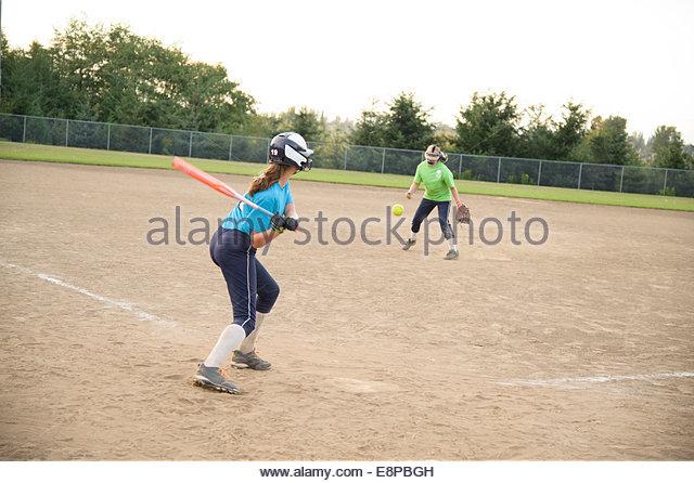Girl (10-12) (13-15) playing baseball - Stock-Bilder