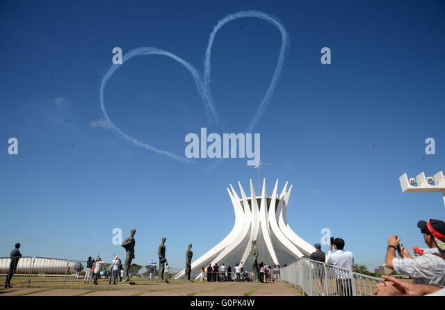 An aircraft creates a heart shape from smoke over the Brasilia Cathedral at the start of the Olympic flame relay - Stock Image