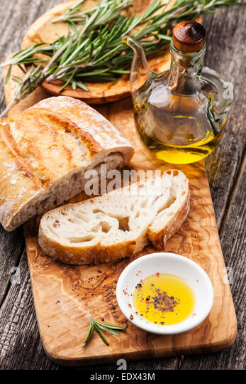 Sliced bread Ciabatta and extra virgin Olive oil on olive wood cookware background - Stock-Bilder