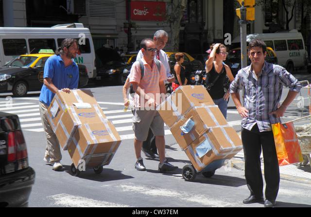 Buenos Aires Argentina Avenida de Mayo street scene Hispanic man woman crossing pedestrian dolly hand cart pushing - Stock Image