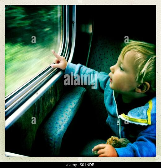 Young boy looking out of a train window, UK - Stock Image
