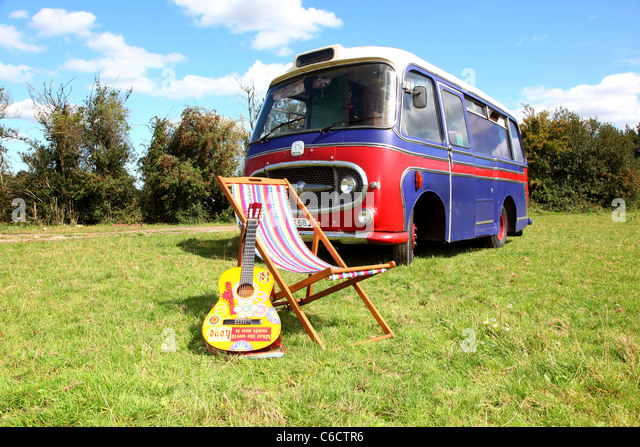 1971 Bedford camper van parked in a field, with an acoustic guitar and a deckchair in the foreground. - Stock Image
