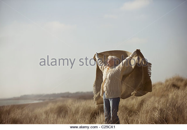 A senior woman standing amongst the sand dunes, holding a blanket into the wind - Stock Image