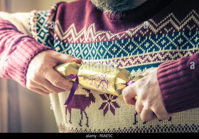 Person pulling christmas cracker alone - Stock Image