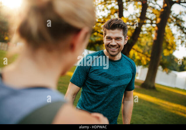 Shot of handsome and fit young man smiling with woman in park. Young couple at park. - Stock Image
