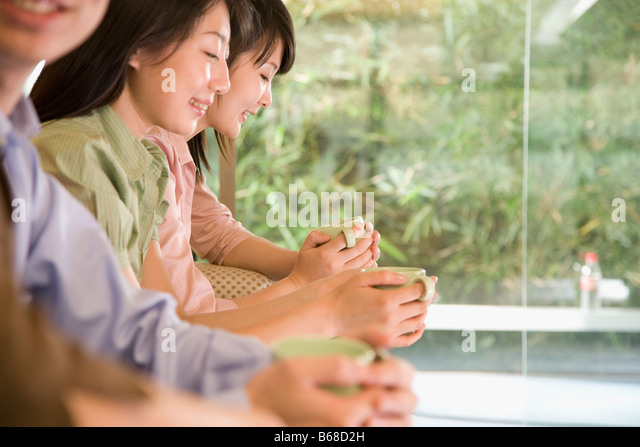 Office workers holding coffee cups and smiling - Stock Image