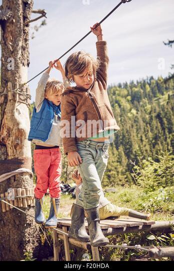 Two children walking across single rope bridge - Stock Image