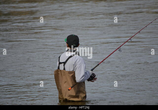 Fisherman with casting rod & reel in waders at the base of Conowingo Dam on Susquehanna River in Harford County - Stock Image