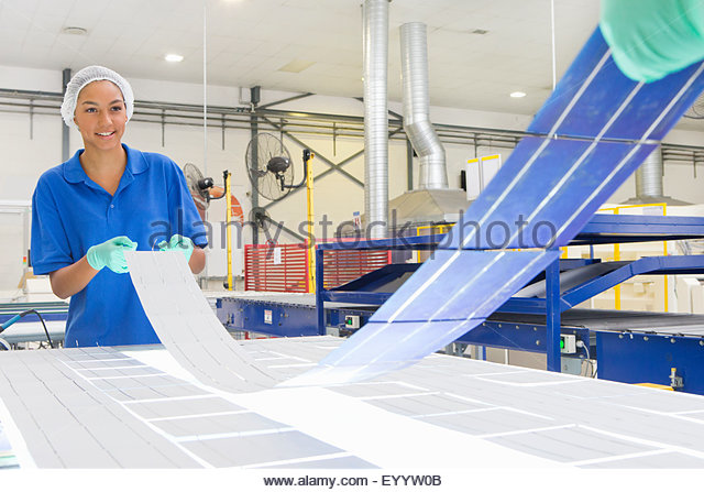 Technicians arranging solar cells to form solar panel on factory production line - Stock Image