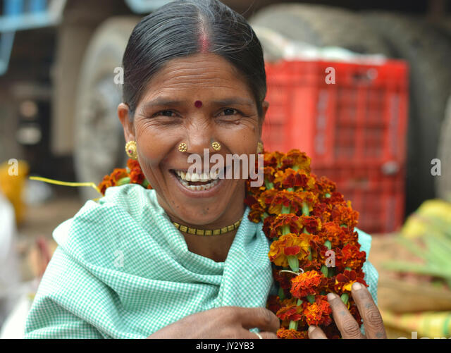 Closeup street portrait of a smiling and laughing mature Indian Adivasi market woman, carrying a flower garland - Stock Image