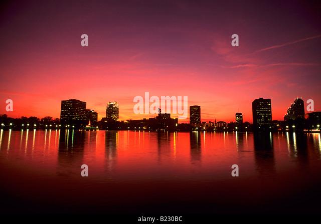 Reflection of buildings in water at dusk, Lake Eola, Orlando, Orange County, Florida, USA - Stock Image