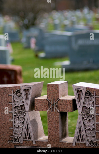 A cross atop a granite tombstone in Christ our Redeemer Catholic Cemetery, Pittsburgh, Pennsylvania . - Stock-Bilder