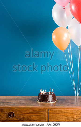 Birthday cake and balloons - Stock Image