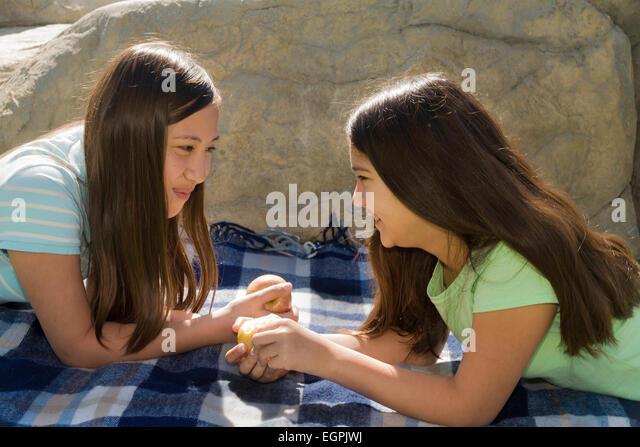 13 year oldVietnamese-Caucasian and Hispanic Mexican Caucasiann girls share fruit.MR  © Myrleen Pearson - Stock-Bilder