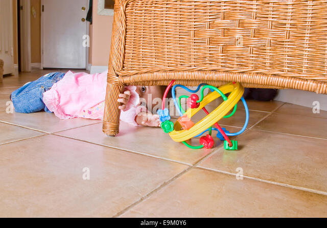 9-month-old Colombian baby girl crawls toward brightly colored toy hidden under rattan chair at home. MR  © - Stock-Bilder