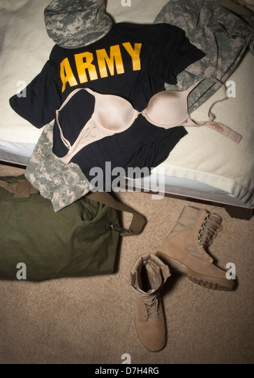 Women's Army Combat (ACU) camouflage hat, pants, desert Combat boots, Duffel bag, tee-shirt and bra on a civilian - Stock Image