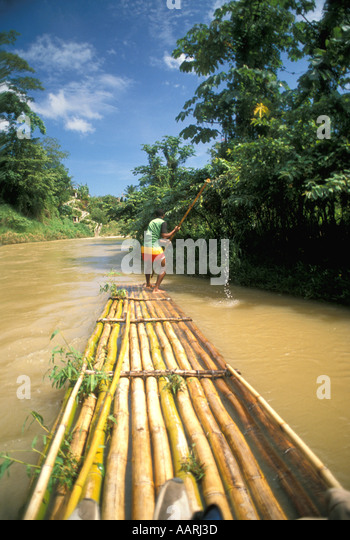 Jamaica River Rafting on Bamboo Raft on Martha Brae River near Montego Bay with action of guides rafting pole. - Stock Image