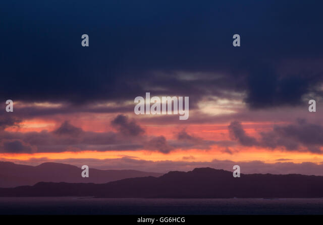 Sunrise breaking over the Applecross mountains of Wester Ross with the Isle of Raasay in the foreground. - Stock Image